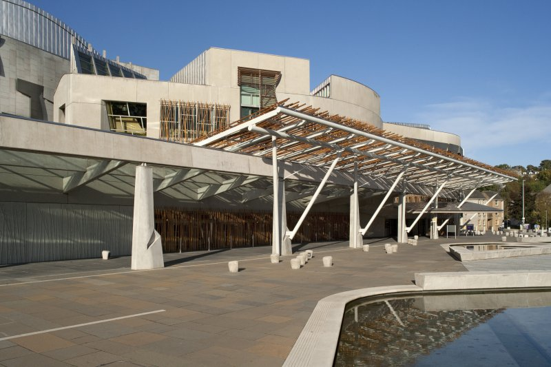 View looking north-west across the entrance plaza of the Scottish Parliament to the canopied walkway, pergola and main entrance