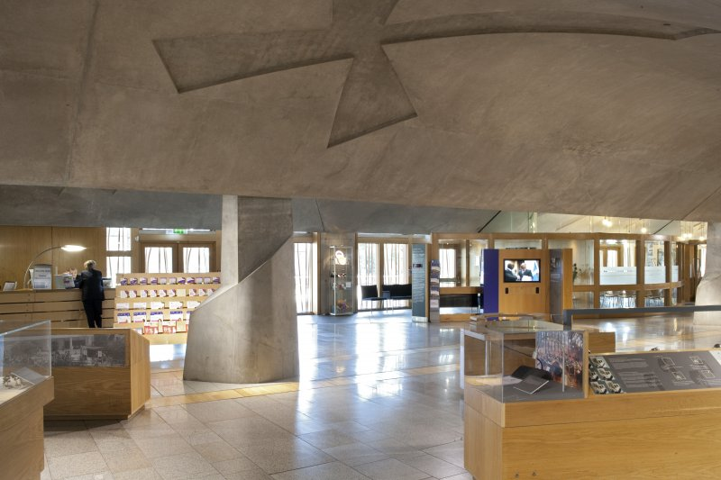 View looking south east across the main hall of the Scottish Parliament, including a ceiling vault and display panels, towards the glazed east wall