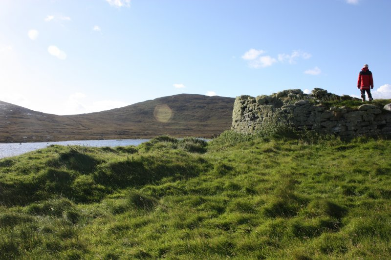A view to the broch, looking over the remains of a later building, taken from the NNE.