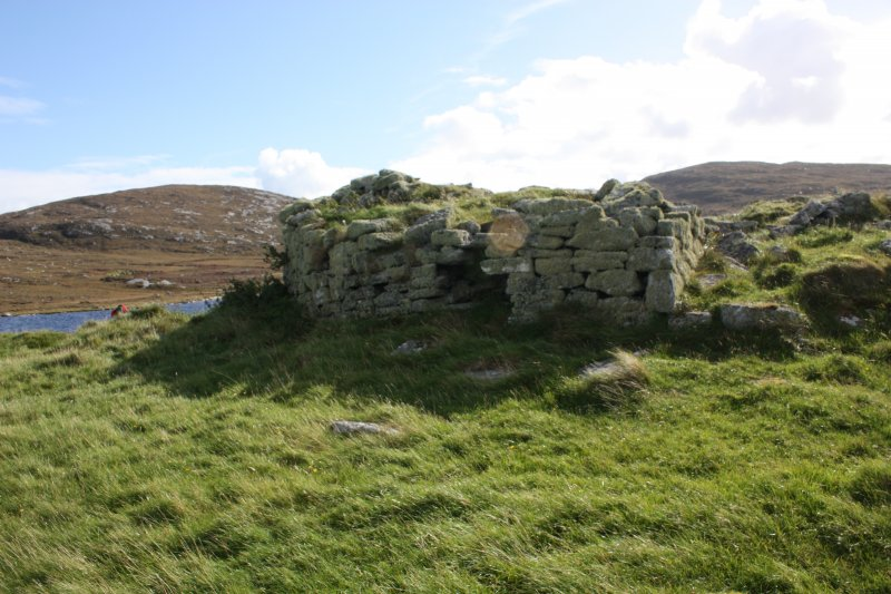 The broch from the N showing the subsiding broch wall (at centre) and the reconstructed entrance to the later buidling (at right).