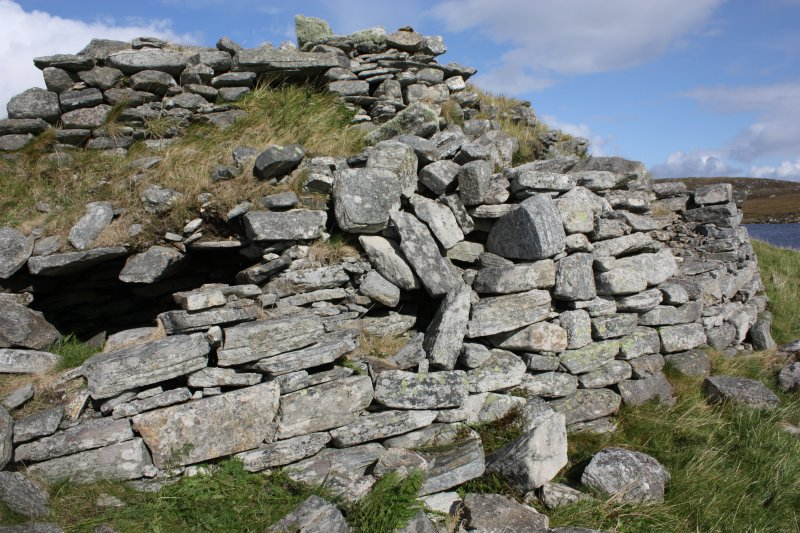The broch wall at the SSW. Their is subsidence in the main broch wall, and the collapsing guard cell roof is visible at left. The internal gallery wall face in the upper part of the photograph has probably been remodelled and the small opening is likely to be a later feature.