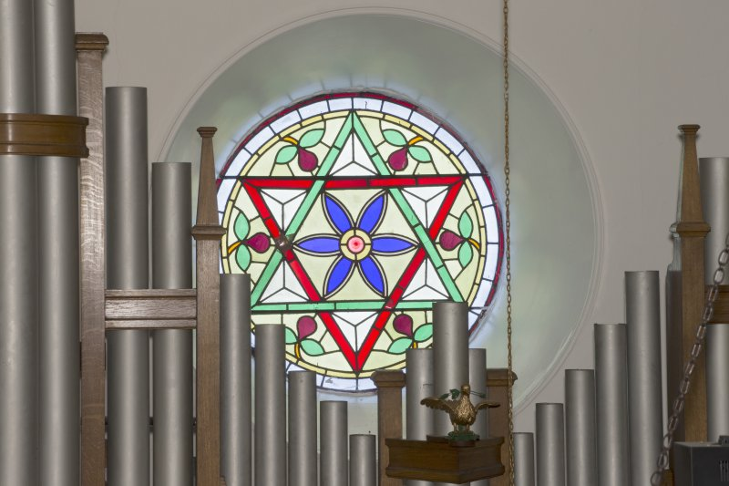 Interior. Detail of round stained glass window to centre of south wall