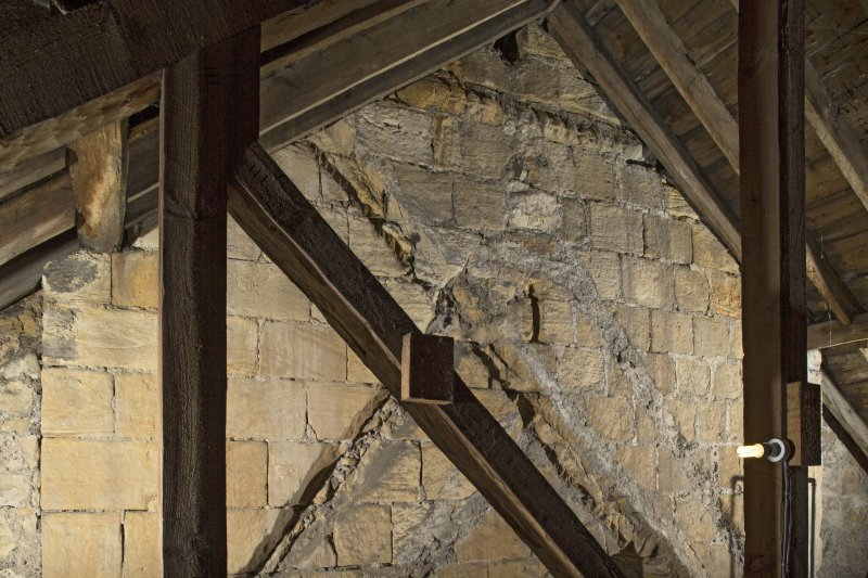 Interior. View within the roof space of the church, showing the raggles of earlier roofs and the decorative string course on the tower's east face, 2nd stage