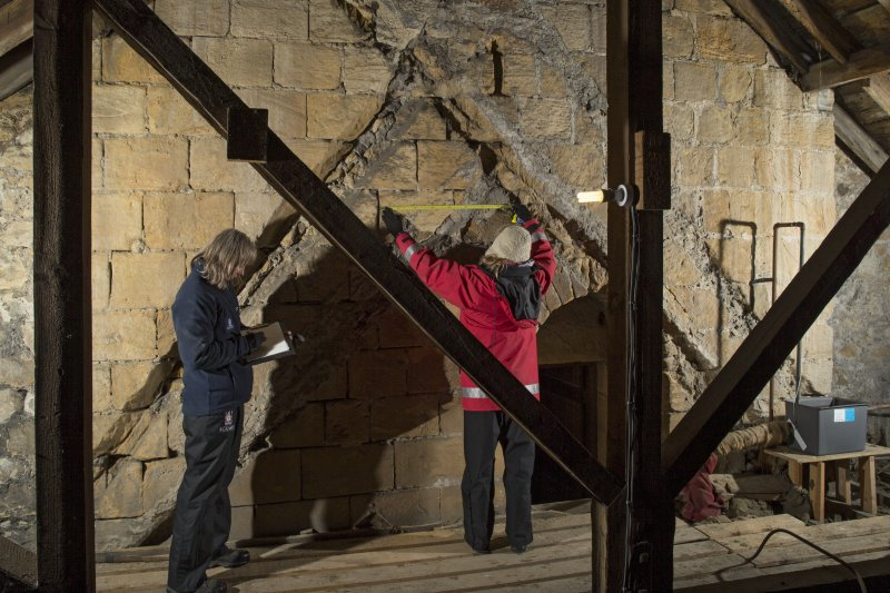 Interior. View within the roof space of the church, showing the raggles of earlier roofs on the tower's east face, 2nd stage, with RCAHMS surveyors making a measured survey