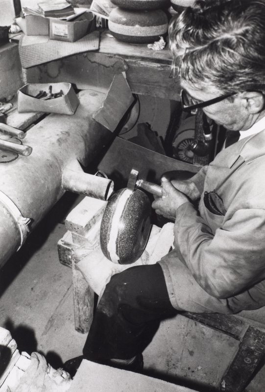 Interior. Leafield House, former factory office and dressing area.  Process: Finishing. Hand dressing the striking band (known as belting) of a curling stone. Note the dust extractor. c.1975, James Wyllie.