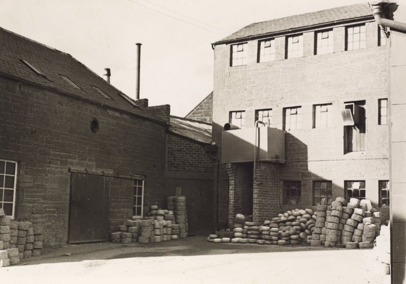View of site from SW prior to taking down of 3 storey  building, formerly a Mauchline Box-making factory. The disused Rough Out Shed of the curling stone factory is on the left.