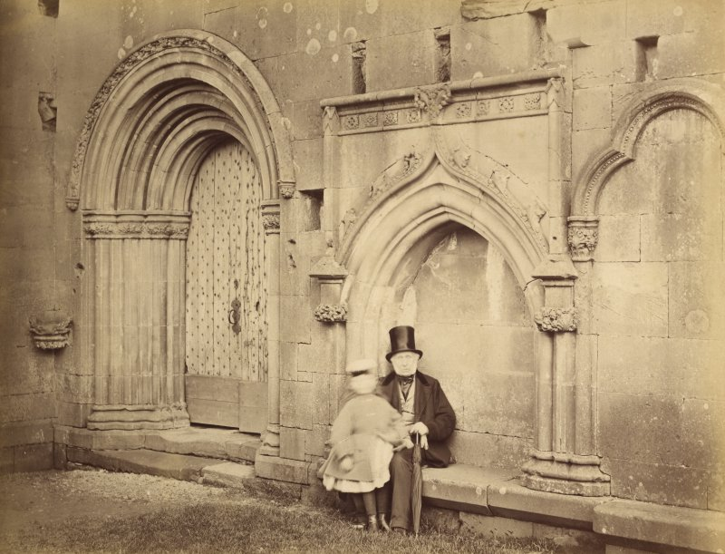 View of processional doorway and seat with man and child, Melrose Abbey.