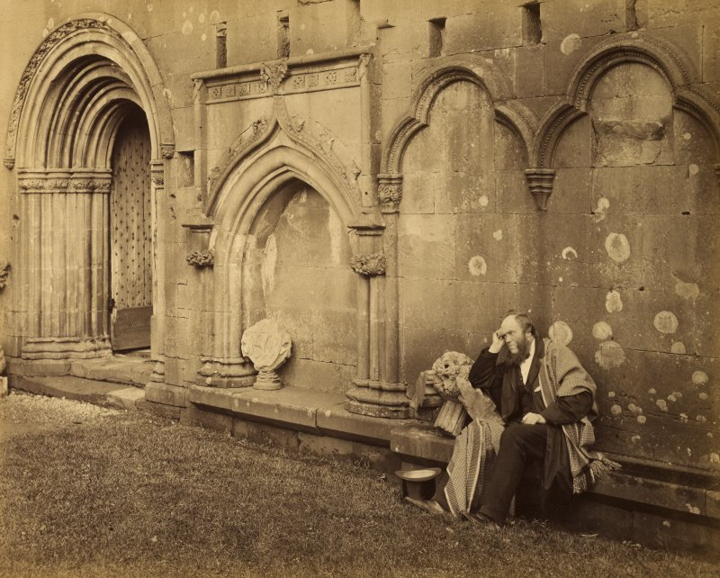 View of processional doorway to the west and seated man, Melrose Abbey.
