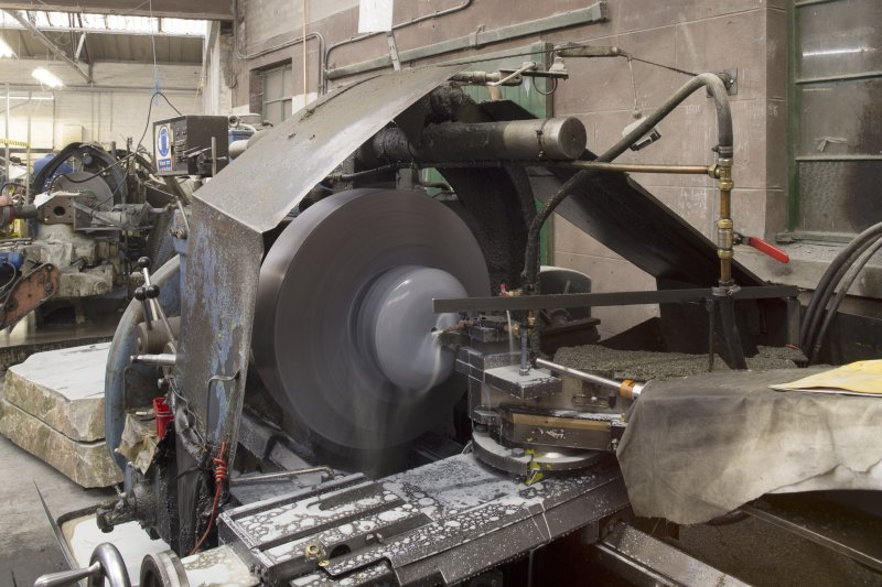 Interior. Main Workshop. Turret of Lathe 1, Roughing-out machine. Block or rough-cut common ailsa stone from vertical corer no. 2 is being fashioned.