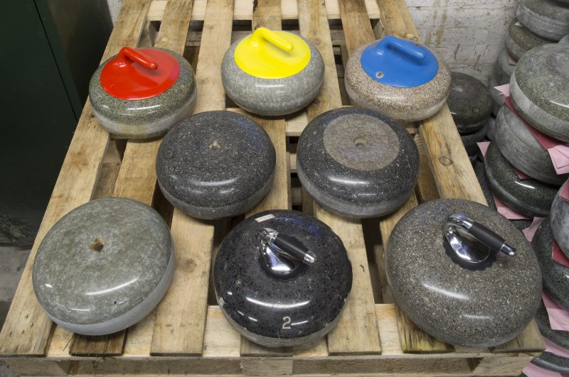 Interior. Dispatch Shed. Curling Stones, Top Row left to right:  (red handle) Outdoor common ailsa upto year 2000 with ailsert on one side only, 40lbs in weight; (yellow handle)  Indoor blue hone, 1970s, 40lbs in weight; (blue handle) Indoor Furnace Loch Fyne granite, c.1930s-1940s, 38-40lbs in weight Middle Row left to right: Indoor Blue Trevor Stone (Wales), c.1960s, 40lbs in weight; Indoor Blue Trevor hybrid with ailsa craig ailsert, stone c.1960s, ailsert c.1995 Bottom Row: Outdoor ailsa craig blue hone, c.1930s - early 1950s, 38lbs in weight; Outdoor Crawford John , c.1900, 32-34llbs in weight
