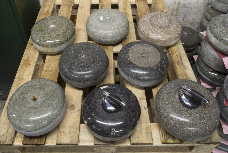 Interior view of Kay's Curling Stone Factory, Mauchline. Dispatch Shed. Curling Stones, Top Row left to right:  Outdoor common ailsa upto year 2000 with ailsert on one side only, 40lbs in weight; Indoor blue hone, 1970s, 40lbs in weight; Indoor Furnace Loch Fyne granite, c.1930s-1940s, 38-40lbs in weight Middle Row left to right: Indoor Blue Trevor Stone (Wales), c.1960s, 40lbs in weight; Indoor Blue Trevor hybrid with ailsa craig ailsert, stone c.1960s, ailsert c.1995 Bottom Row: Outdoor ailsa craig blue hone, c.1930s - early 1950s, 38lbs in weight; Outdoor Crawford John , c.1900, 32-34llbs in weight