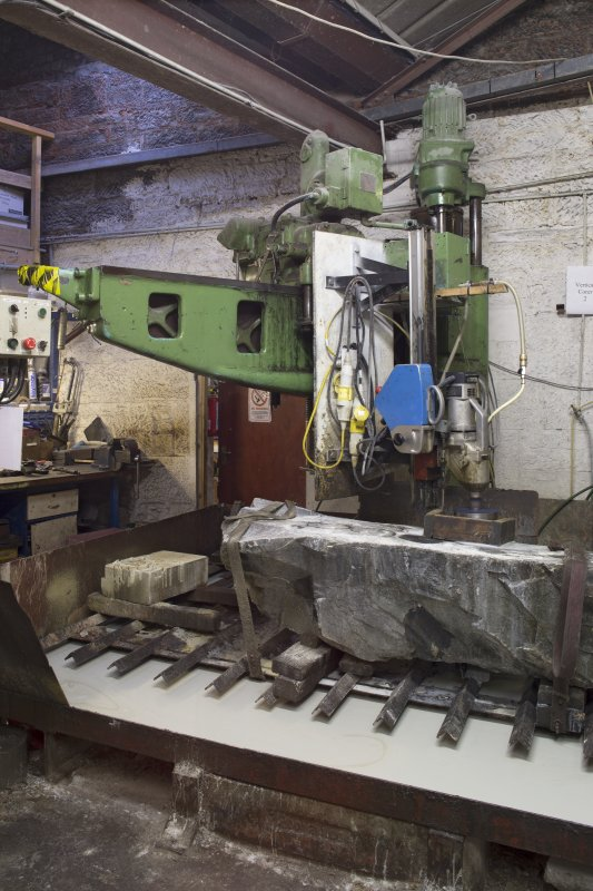 Interior. Main Workshop. Corer 2. This drill cuts the ailserts. Aislerts are disks which are inserted into the body of the curling stone and provides the running edge over the ice. Modern stones have 2 ailserts to enable double the use before replacing or reconditioning of stones needs to take place.