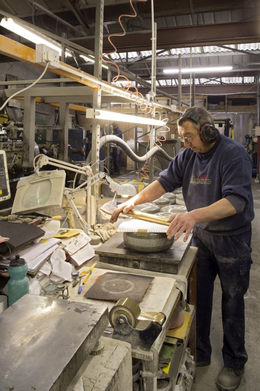 Interior. Main Workshop. Finishing. After the running edge is rubbed on emory paper, carbon paper is then placed on the running edge and a brass roller is run over it to produce a 'print' of the running edge surface. This is then sent to be measured and checked to ensure that the running edge is within specification allowing the pairing of stones prior to dispatch.
