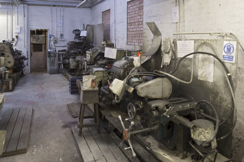 Interior. Main Workshop/Giftware. Here we see lathes 5, 6 and 7. Lathe 5 is the banding lathe which shapes the striking band on the stones. This is made by Lang. Lathe 6 is used to undercut the circular pocket in giftware curling stones for metal finishings, and is a Ward 3DB Capstan or turret lathe made by H W Ward and Co. Worcester, England. Lathe 7 is used to drill the metal fittings holes in the curing stone giftware blanks. This is a Herbert No. 5 Senior lathe.