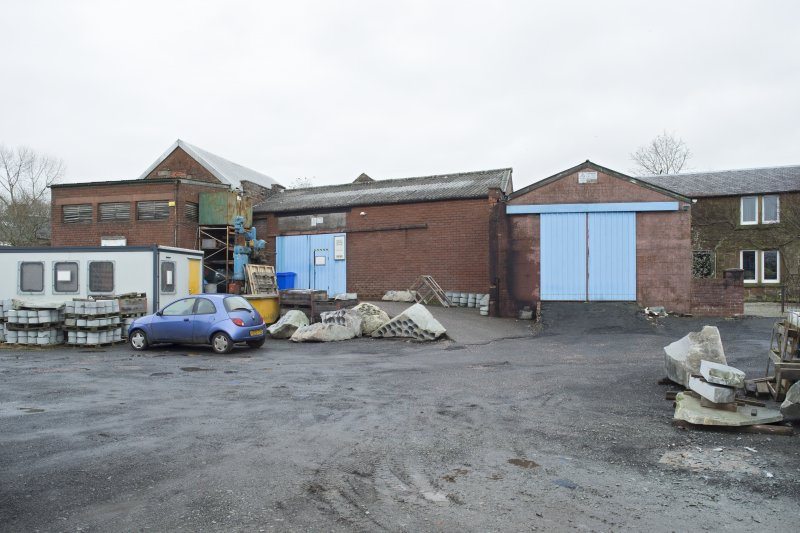 General view of site from south showing former roughing out shed (left, double pitch roof with former extractor unit house (disused) in front), main entrance into main workshop (partial 1949 extension to infill existing courtyard), dispatch shed (blue doors/ double pitch roof) and Leefield House (former house with ground floor extension which contained finishing area, below).