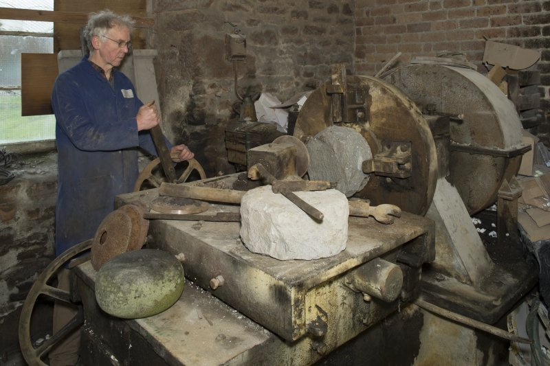 Interior. Rough Out Shed. Ground floor. Rough Out machine (disused since 1980s), installed by Andrew Barclay (Kilmarnock) c.1959. Machine set up to show block in place  and roughed out block on machine in foreground. Mr Jmes Wyllie, owner, demonstrates the machine showing how the cutting tool would be brought across the face of the bock to be cut.