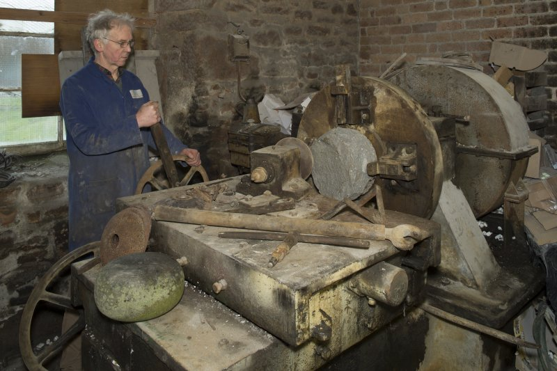 Interior. Rough Out Shed. Ground floor. Rough Out machine (disused since 1980s), installed by Andrew Barclay (Kilmarnock) c.1959. Machine set up to show block in place  and roughed out block on machine in foreground. Mr James Wyllie, owner, demonstrates the machine showing how the cutting tool would be brought across the face of the bock to be cut