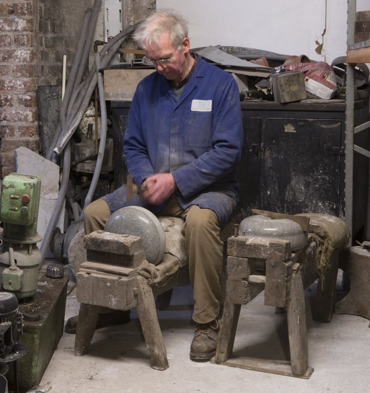Interior. Rough Out Shed. Ground floor. View of 'cuddies'. The cuddy on the left was for cutting the strike band on the curling stone (also known as belting). On the right, the cuddy for cutting square counter sink for handle fittings. Disused since 1980s. Mr James Wyllie demonstrates how these were used.