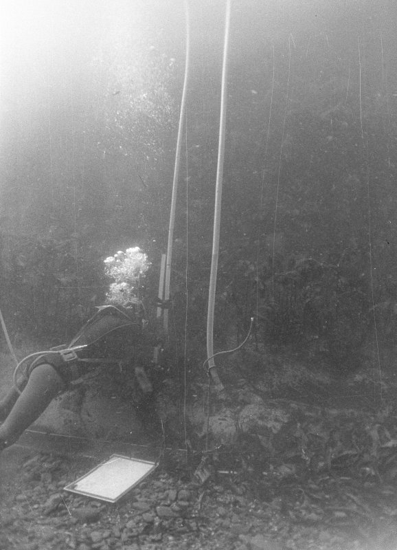 Tony Long using an inverted air-filled hose to determine relative levels on the wreck-site (1977).