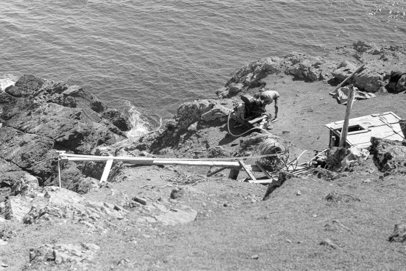 The cliff-top base with (from left to right) the gantry, the air-hose reels, the compressors for the divers' air and the airlift, and the site-hut (1977).
