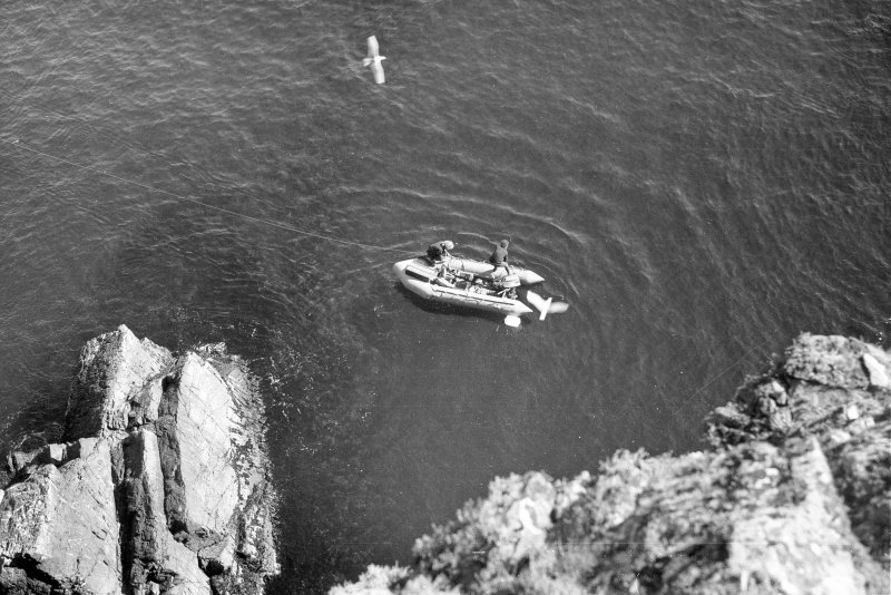 The inflatable boat moored over the site, seen from the cliff-top. (1977)
