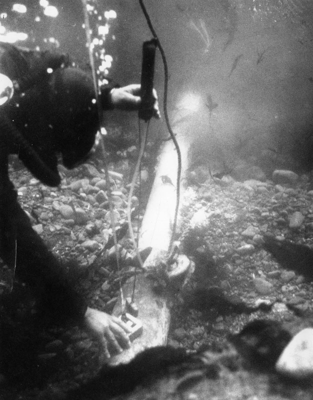 Colin Martin checks the depth of the bronze media sacre shortly after its discovery (1970). (Sydney Wignall)