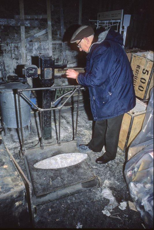 Andrew Williamson, curator of the Shetland Museum, weighing one of the lead ingots (1986).