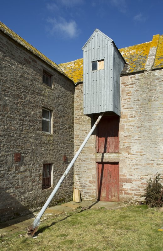View of entrance bay on south wall of mill, with projecting grain elevator up to 3rd floor and doors to kiln at ground.