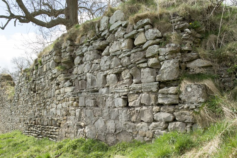 Oblique view of the secondary stonework of the Teviotside curtain wall of Roxburgh castle showing joist holes, from the E