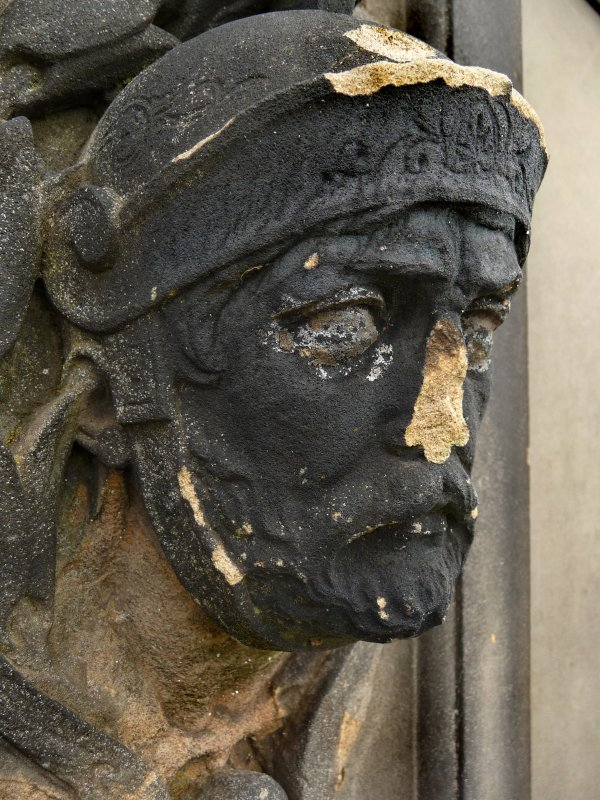 Detail of head of monument, damaged with nose missing, Glasgow Necropolis.