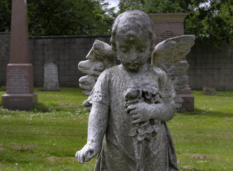 Detail of a statue of an angel, weathered. Morningside Cemetery, Edinburgh.