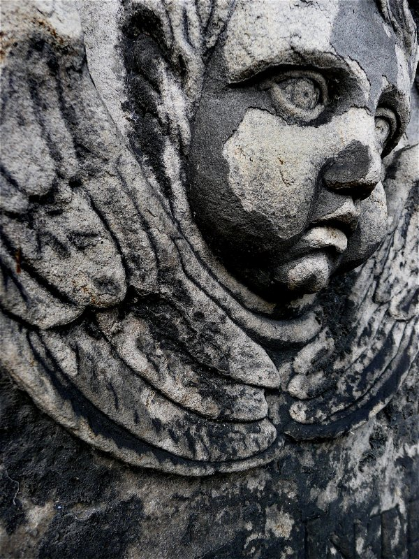 Detail of relief showing face and wings of angel, Old Calton Burial Ground, Edinburgh.