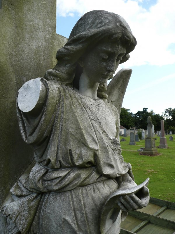 Detail of a statue of an angel reading, with arm missing. Morningside Cemetery, Edinburgh.