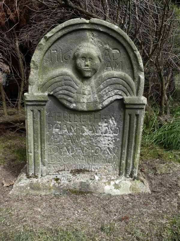 Detail of headstone showing the head and wings of an angel, in memory of Euphan Davidson, c.1716. Currie Kirk Cemetery, Edinburgh.