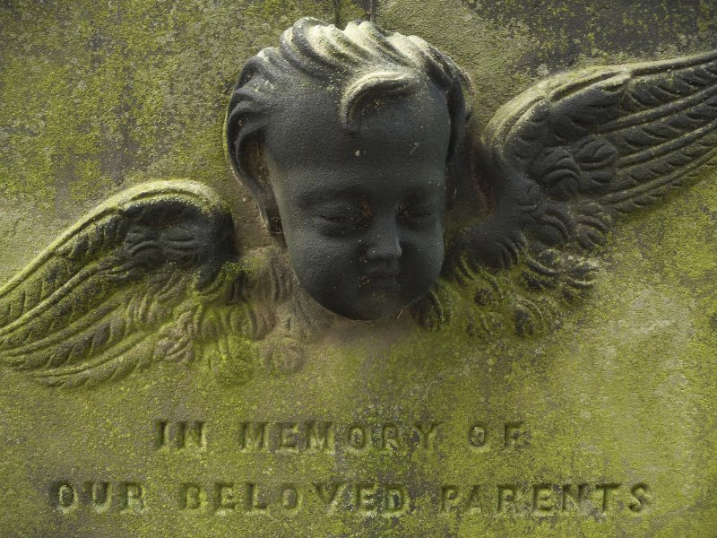 Detail of headstone relief of the head and wings of an angel, 'in loving memory of our parents', Canongate Kirk Cemetery, Edinburgh.