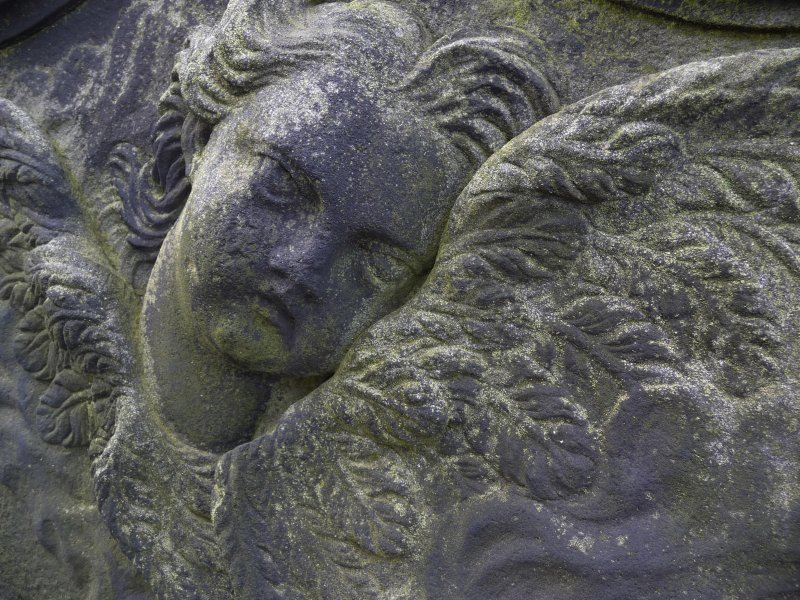 Detail of relief showing the face and wings of an angel, Canongate Kirk Cemetery, Edinburgh.