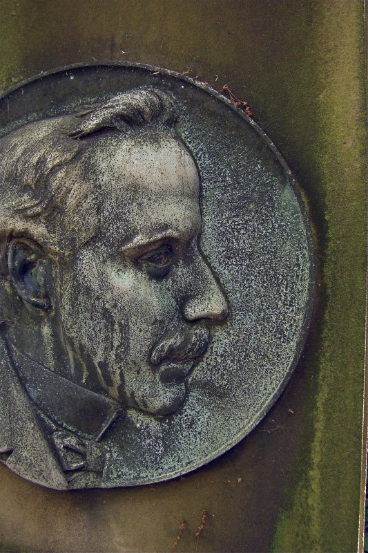 Detail of relief showing the profile of a man's face from the gravestone of William Campbell, organist. Newington Cemetery, Edinburgh.