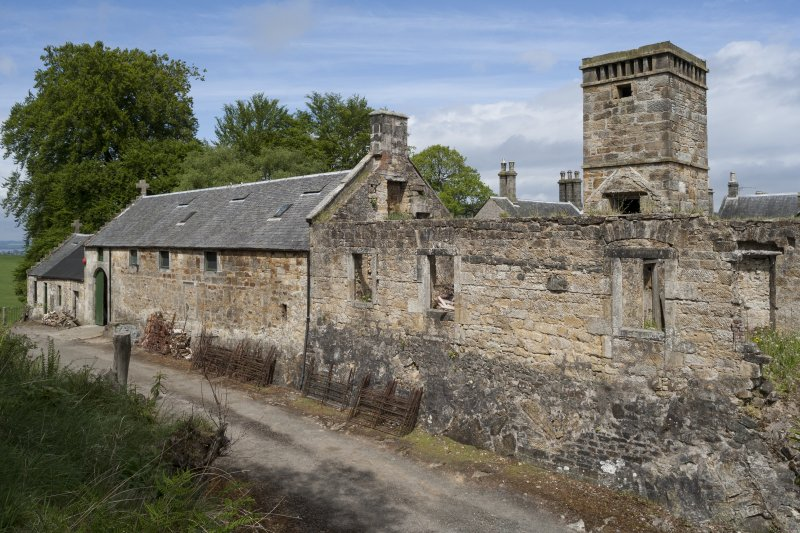 General view of West wing from South showing ruin, old clock tower and stables.