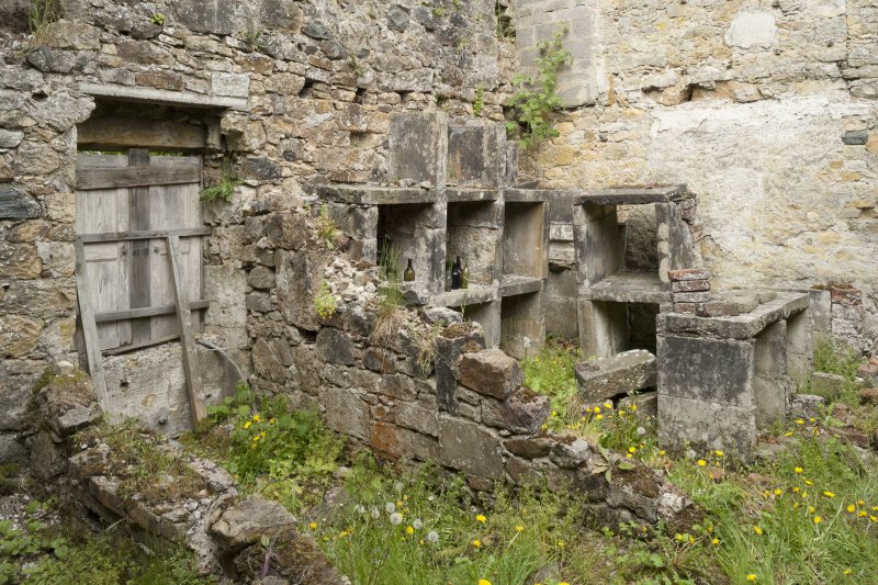 General view from Soth East of ruin on West wing showing stone shelves.