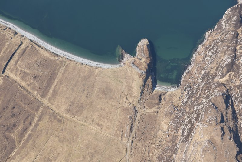 Oblique aerial view of Dun Canna fort and the adjacent fish trap, looking W.