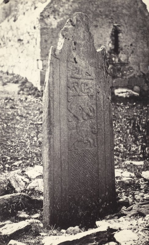 View of face of carved stone cross shaft fragment, supposodly stands at a saints grave in St. Cormac's Chapel ruins, Eilean Mor, Argyll and Bute. Titled: '135. At Ealan Mor.' PHOTOGRAPH ALBUM NO 186: J B MACKENZIE ALBUMS vol.1