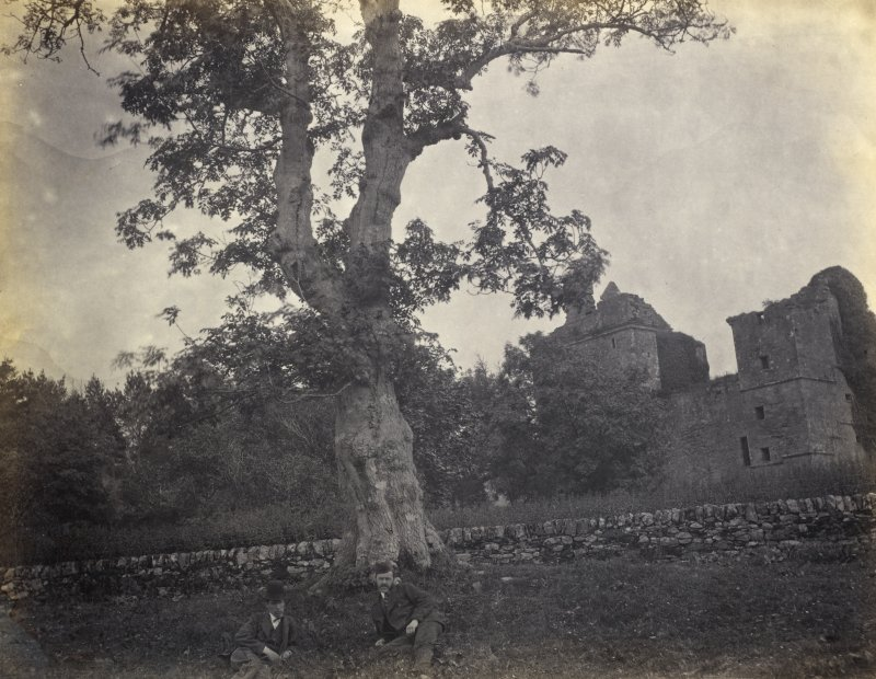 View of Carnasserie Castle, a ruined tower house, with two male figures seated in foreground, at Kilmartin, Argyll and Bute. Titled: '182. Carnassary Castle.' PHOTOGRAPH ALBUM NO 186: J B MACKENZIE ALBUMS vol.1