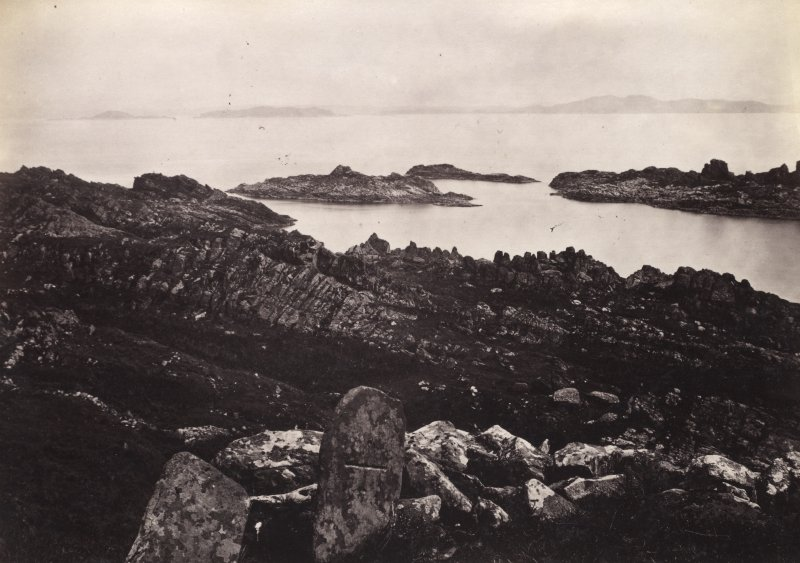 View, wide-angle, of ruins at Eileach An Naoimh, Argyll. There is an incised cross-slab in the foreground. Titled: '46. On Ealan Naomh, locally regarded as the tomb of St. Columba's mother.' PHOTOGRAPH ALBUM, NO 186: J B MACKENZIE ALBUMS vol.1