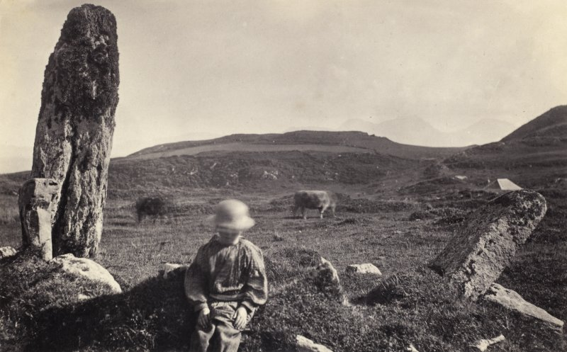 "View of figure in front of one of the two standing stones, originally thought to have been part of a stone circle known as ""Fingal's Limpet Hammers,"" at Lower Kilchattan, Colonsay. Titled: '104. Above the XXX at Scalasaig on the road to Kiloran.' PHOTOGRAPH ALBUM, NO 186: J B MACKENZIE ALBUMS vol.1"