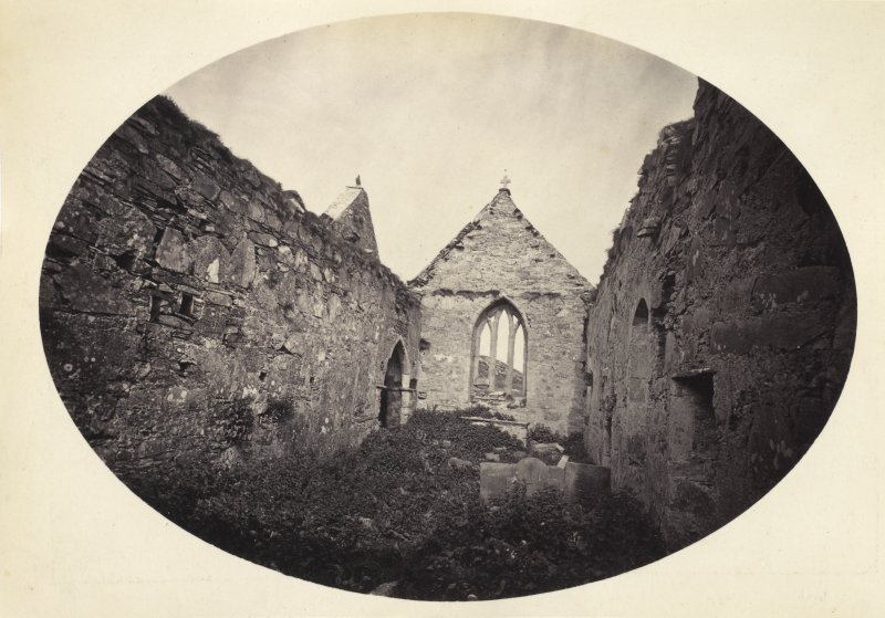 View of overgrown interior ruins of Oransay Priory Church, Oronsay. The Oronsay high cross can be seen to the left of the foreground. Vignetted Photograph. Titled: '60. Interior of Priory Church, Oronsay.' PHOTOGRAPH ALBUM NO 186: J B MACKENZIE ALBUMS vol.1