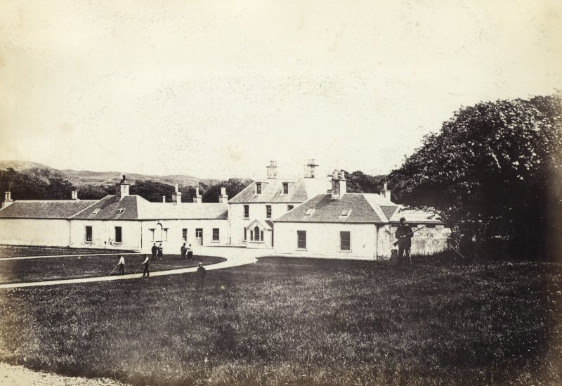 View of front exterior of Colonsay House with various figures in foreground, Colonsay. Titled: '19. Kiloran House, Colonsay.' PHOTOGRAPH ALBUM NO 186: J B MACKENZIE ALBUMS vol.1
