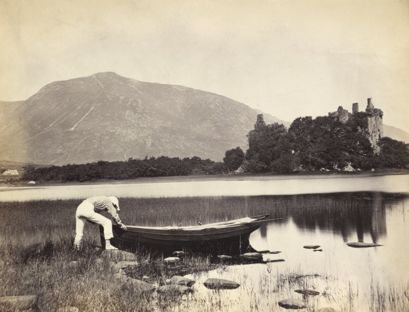 View of figure pushing a boat into Loch Awe in the foreground with Kilchurn Castle in the background, Kilchurn, Argyll and Bute. Titled: '122. Kilchurn Castle, Lochawe.' PHOTOGRAPH ALBUM NO 186: J B MACKENZIE ALBUMS vol.1