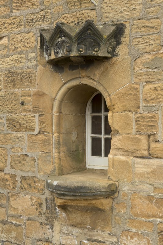 View of reused niche, now a window, on west gable of Session House, including crown canopy stone and floreate capital base.