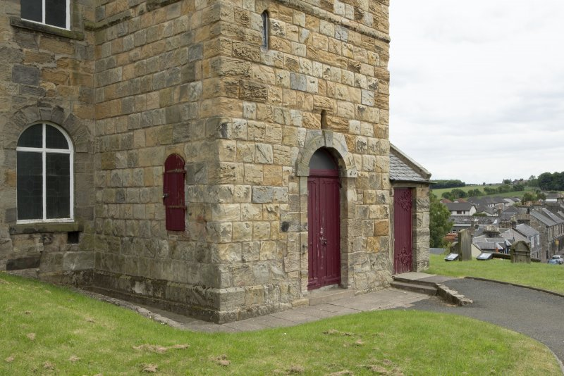 View of ground floor stage of tower, showing small elevated door into spiral stair to north face and later doorway to west.