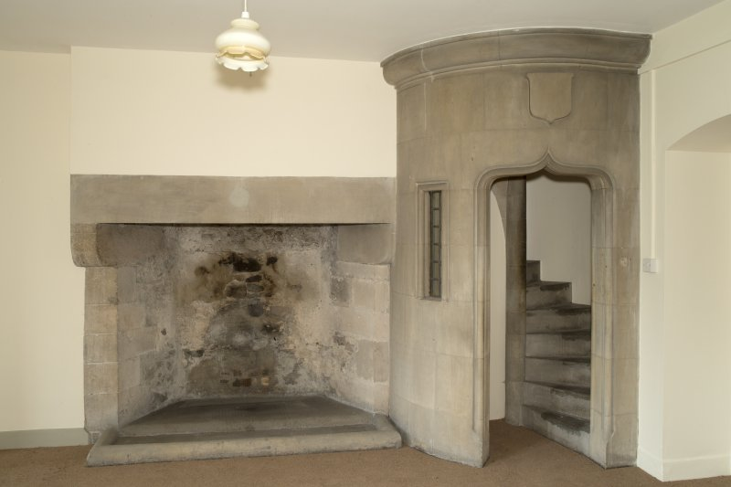 Interior. Ground floor, recreation room, view of fireplace and spiral staircase